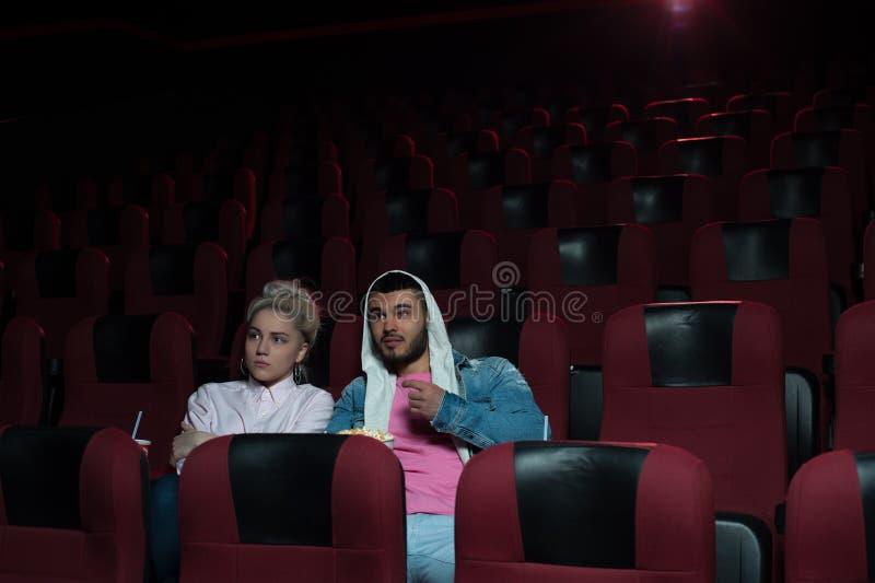 Pares jovenes que se sientan en teatro vacío del cine fotos de archivo