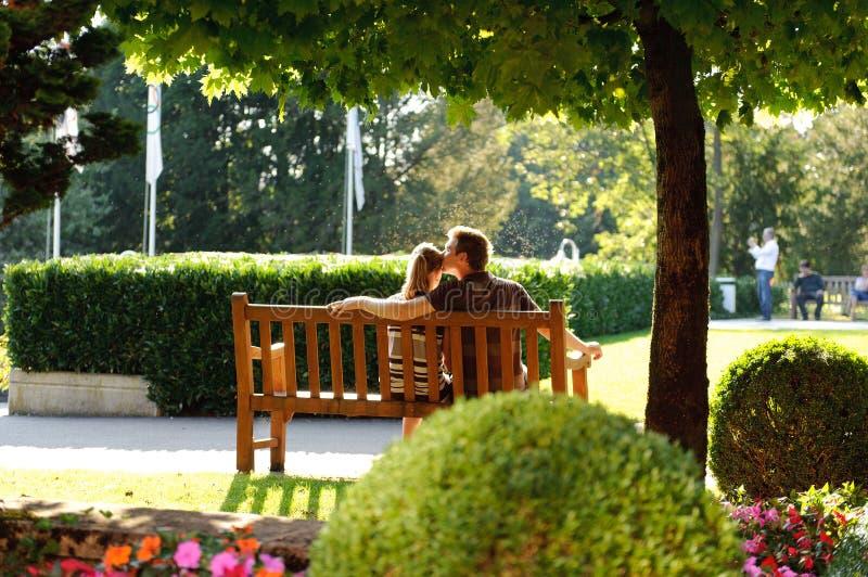 Pares jovenes que se sientan en un banco en el parque imágenes de archivo libres de regalías