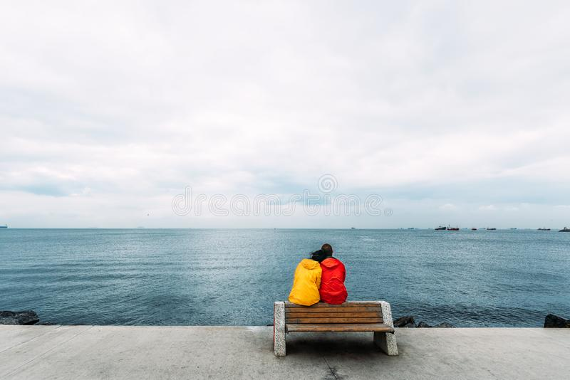 Pares jovenes que se sientan en un banco por el mar El viajar del hombre y de la mujer La gente se sienta en un banco y una mirad fotografía de archivo