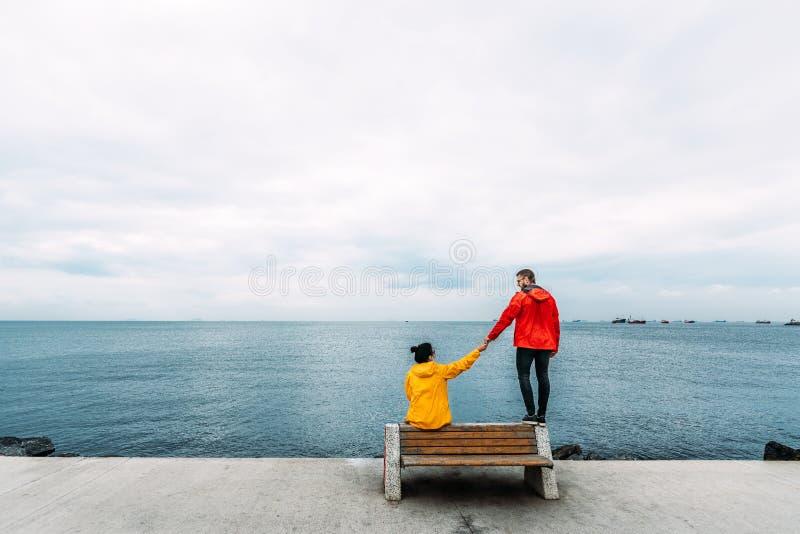 Pares jovenes que se sientan en un banco por el mar El viajar del hombre y de la mujer La gente se sienta en un banco y una mirad foto de archivo