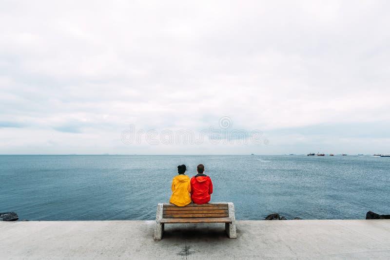Pares jovenes que se sientan en un banco por el mar El viajar del hombre y de la mujer La gente se sienta en un banco y una mirad imágenes de archivo libres de regalías