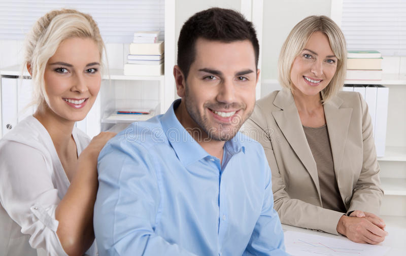 Pares jovenes que se sientan en una conversación de las ventas en el banco o el insuranc fotografía de archivo libre de regalías