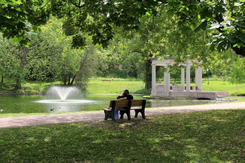 Pares jovenes que se sientan junto en banco de parque fotos de archivo libres de regalías