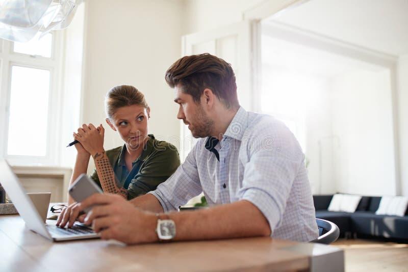 Pares jovenes que se sientan junto en casa con el ordenador portátil imagen de archivo libre de regalías