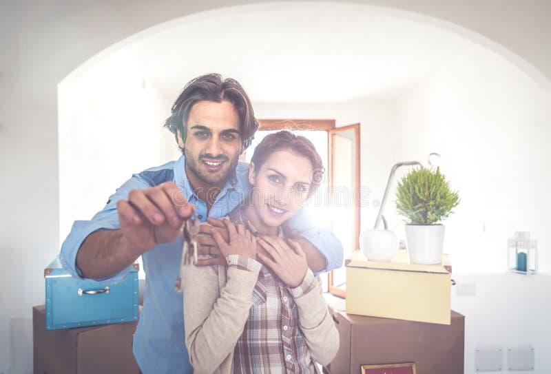 Pares jovenes que se trasladan adentro al nuevo apartamento imagen de archivo