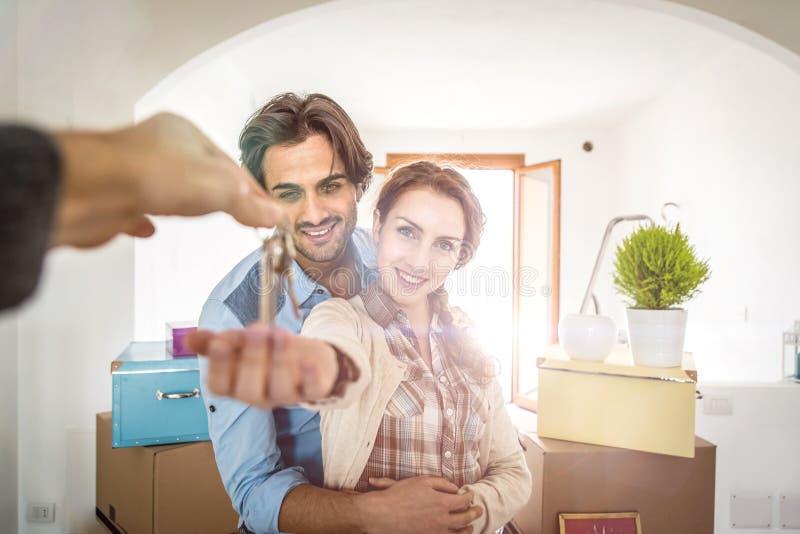 Pares jovenes que se trasladan adentro al nuevo apartamento foto de archivo libre de regalías