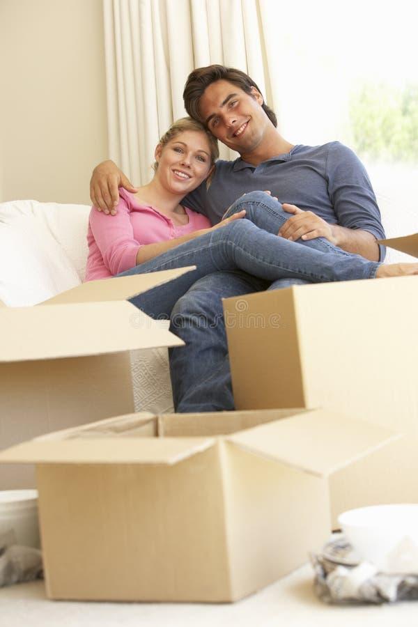 Pares jovenes que se trasladan al nuevo hogar rodeado por las cajas de embalaje fotografía de archivo libre de regalías