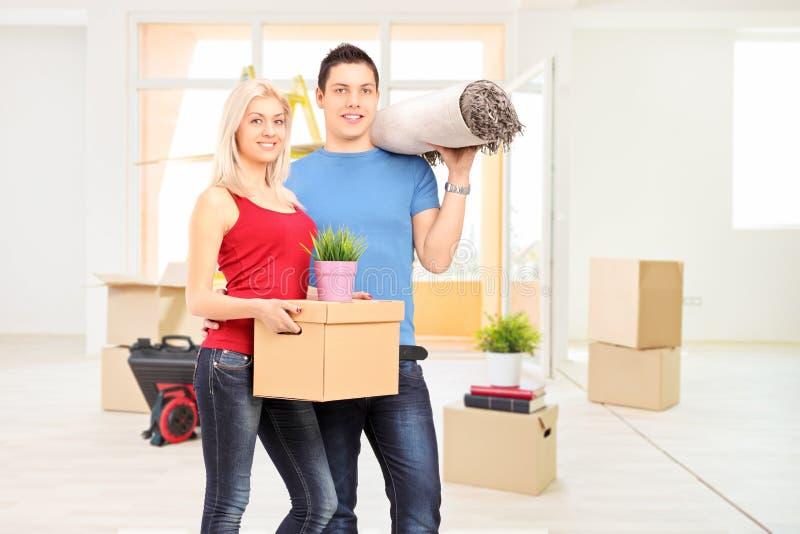 Pares jovenes que se trasladan a un nuevo apartamento imagenes de archivo