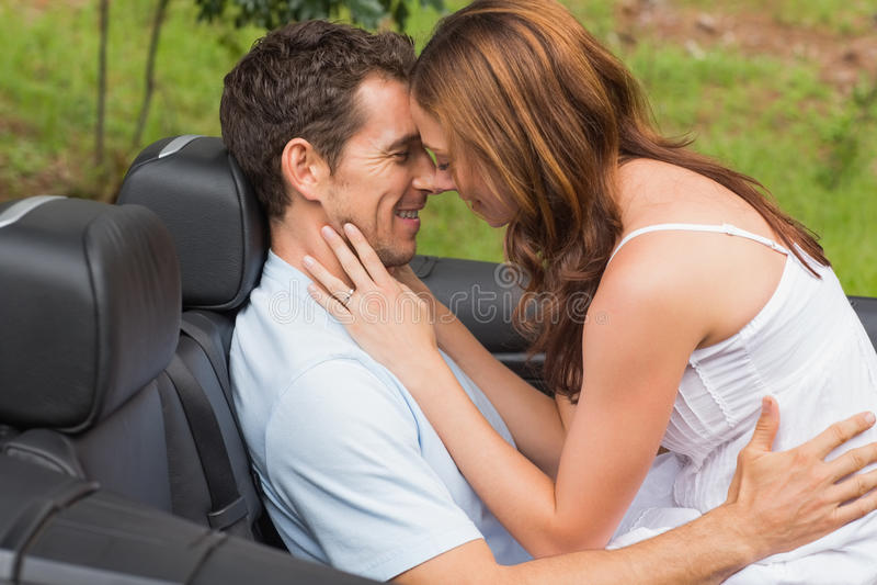 Pares jovenes que sienten románticos en asiento trasero foto de archivo libre de regalías