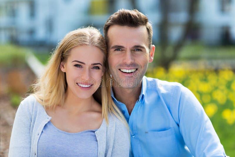 Pares jovenes que sonríen al aire libre fotografía de archivo libre de regalías