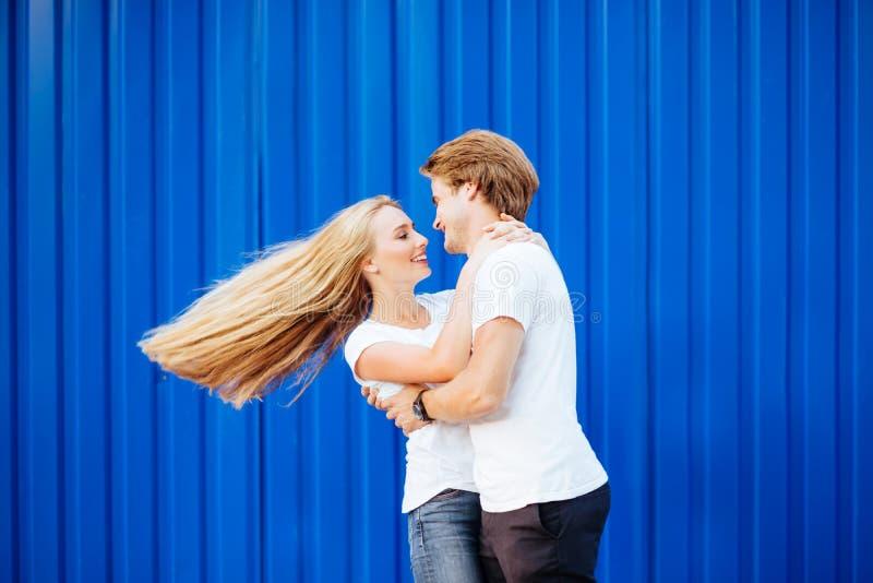 Pares jovenes que sonríen en un fondo azul fotografía de archivo