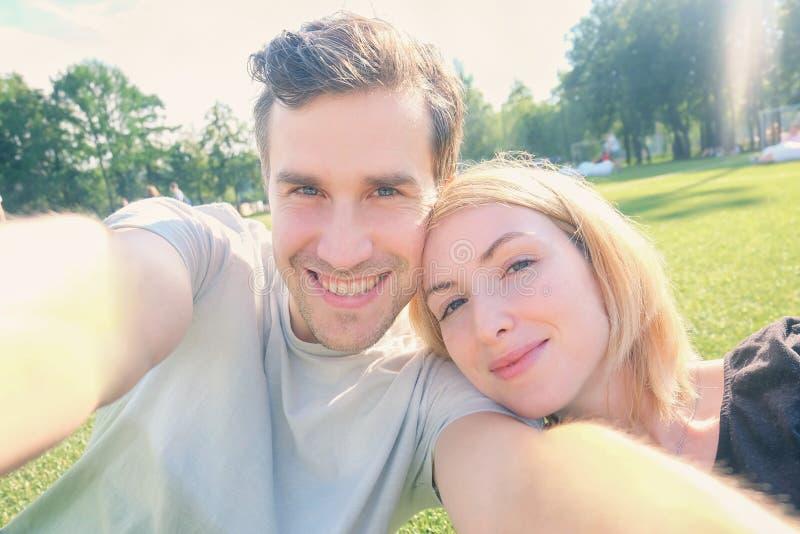 Pares jovenes que sonríen mientras que toma el selfie foto de archivo libre de regalías