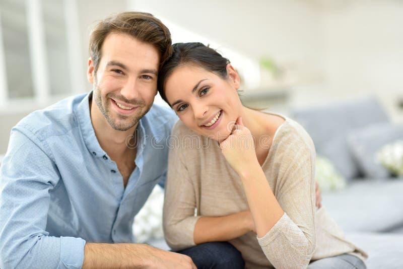 Pares jovenes que sonríen siendo feliz en casa imagen de archivo