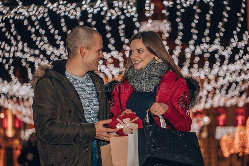 Pares jovenes que sostienen bolsos de compras y que se divierten en la noche fotografía de archivo libre de regalías