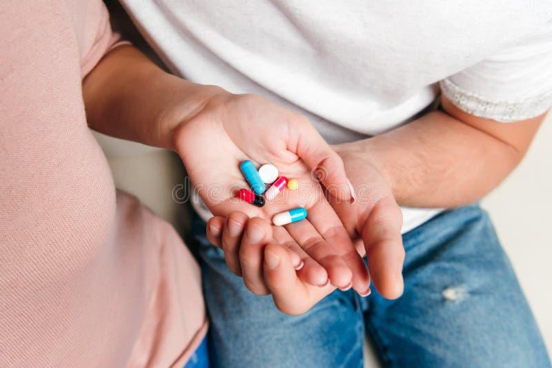 Pares jovenes que sostienen diversas píldoras en las palmas foto de archivo libre de regalías