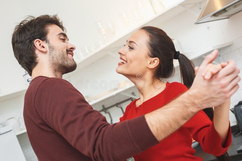 Pares jovenes que tienen igualación romántica en casa en el primer del baile de la cocina fotografía de archivo