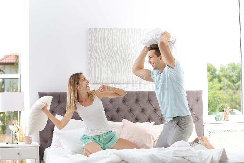 Pares jovenes que tienen lucha de almohada en cama imagen de archivo libre de regalías