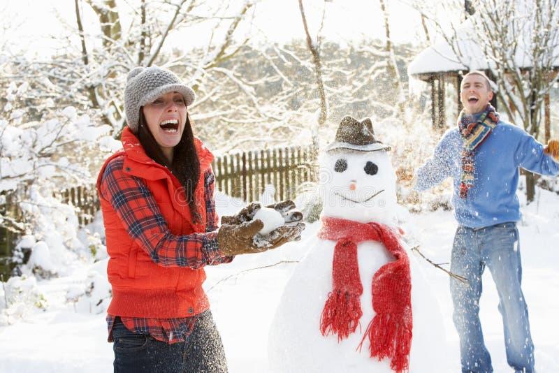 Pares jovenes que tienen lucha de la bola de nieve en jardín imagen de archivo