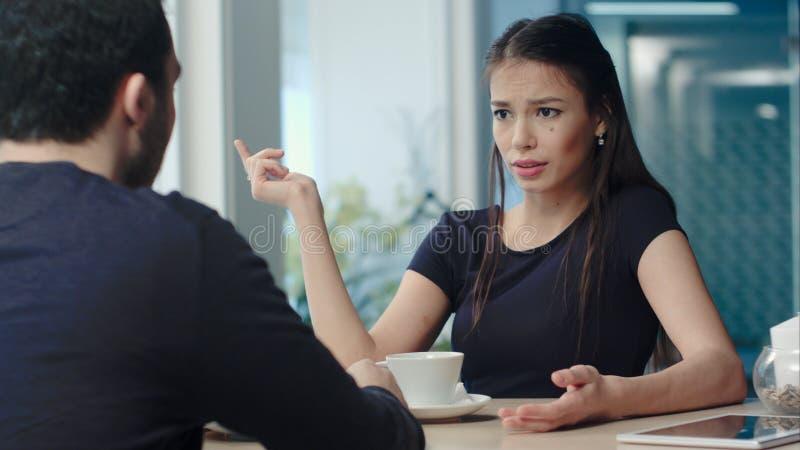 Pares jovenes que tienen una discusión en el café imagenes de archivo