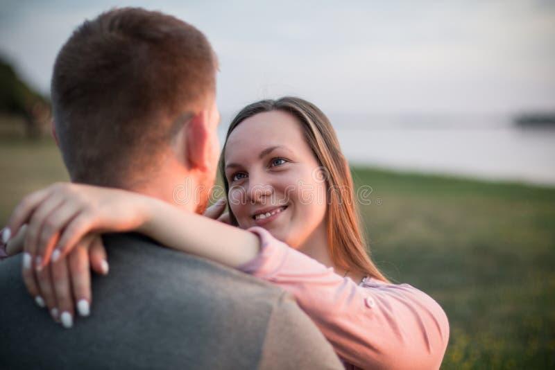 Pares jovenes que tienen una fecha en la playa, sonriendo fotografía de archivo libre de regalías