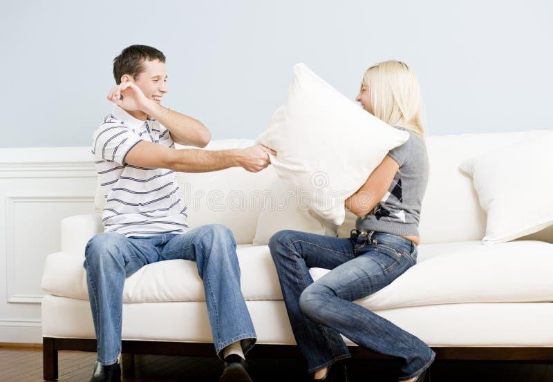 Pares jovenes que tienen una lucha de almohadilla en el sofá fotos de archivo