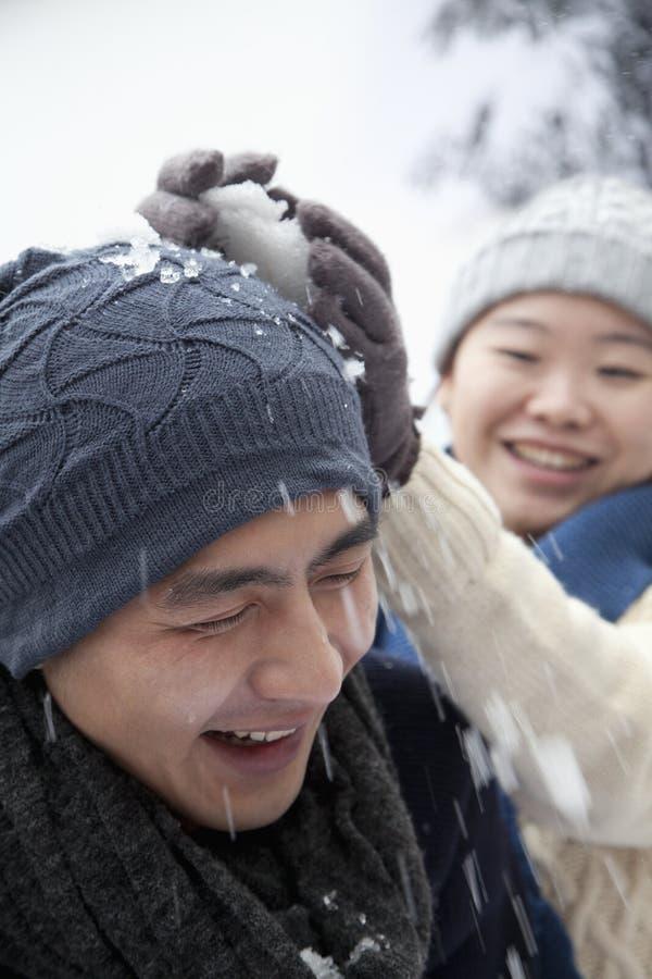 Pares jovenes que tienen una lucha de la bola de nieve, golpe en la cabeza fotografía de archivo