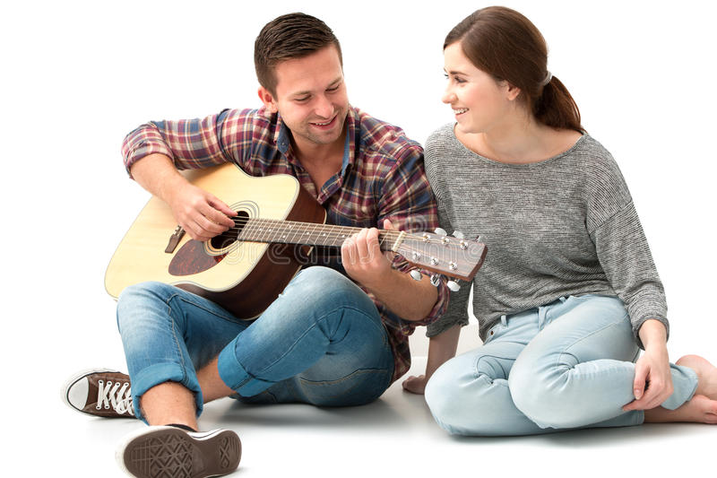 Pares jovenes que tocan la guitarra imagen de archivo libre de regalías