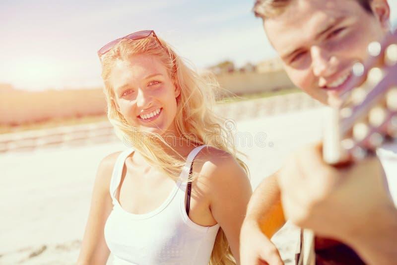 Pares jovenes que tocan la guitarra en la playa en amor foto de archivo