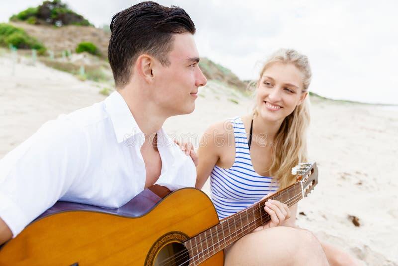Pares jovenes que tocan la guitarra en la playa en amor fotografía de archivo libre de regalías