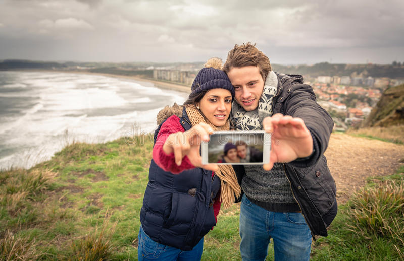 Pares jovenes que toman la foto del selfie con smartphone fotos de archivo
