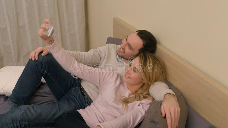 Pares jovenes que toman la foto del selfie usando el teléfono celular, mintiendo en cama en dormitorio en casa fotografía de archivo libre de regalías
