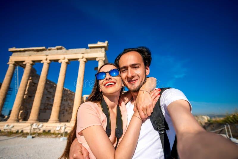 Pares jovenes que toman la imagen del selfie con el templo de Erechtheum en fondo en acrópolis fotografía de archivo libre de regalías