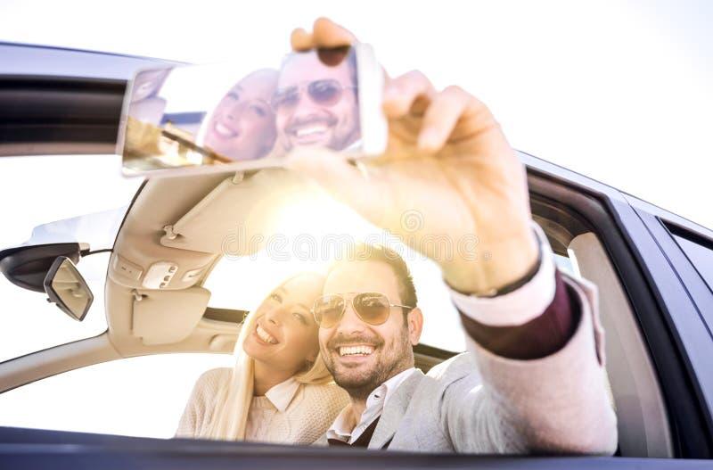 Pares jovenes que toman un selfie en coche fotos de archivo libres de regalías