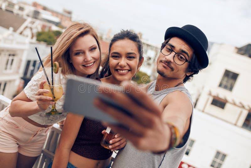 Pares jovenes que toman un selfie en el tejado fotos de archivo libres de regalías