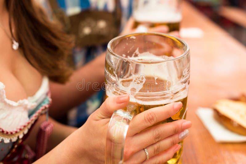 Pares jovenes que tuestan en tienda de la cerveza de Oktoberfest foto de archivo libre de regalías