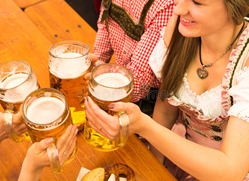 Pares jovenes que tuestan en tienda de la cerveza de Oktoberfest fotografía de archivo