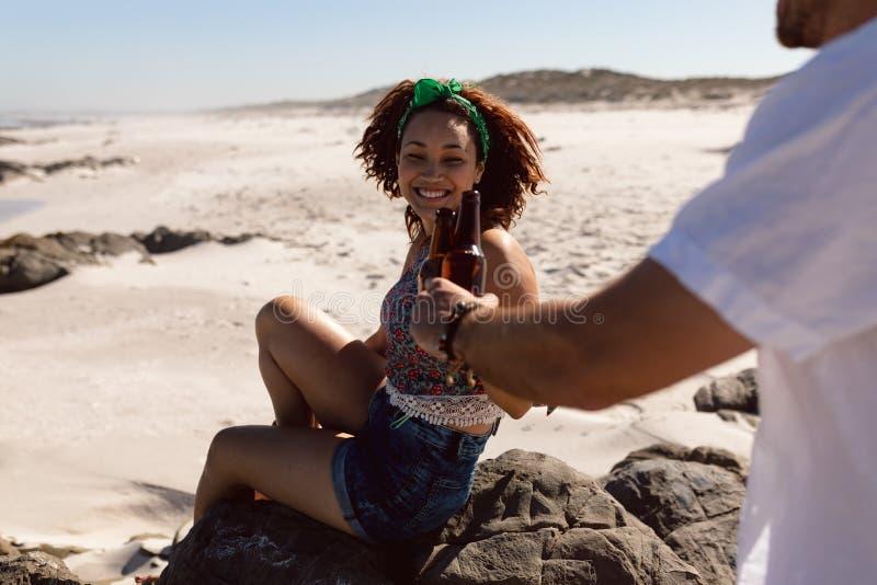 Pares jovenes que tuestan la botella de cerveza en la playa en la sol imágenes de archivo libres de regalías