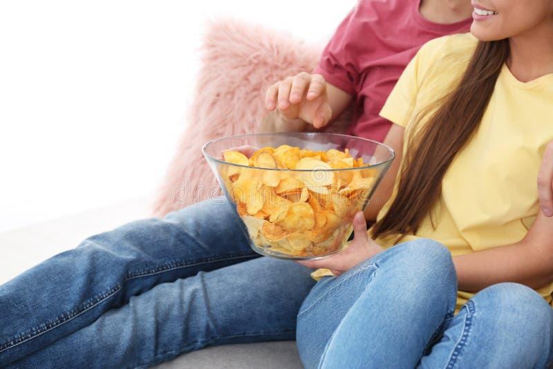Pares jovenes que ven la TV con las patatas fritas en el sofá fotos de archivo libres de regalías