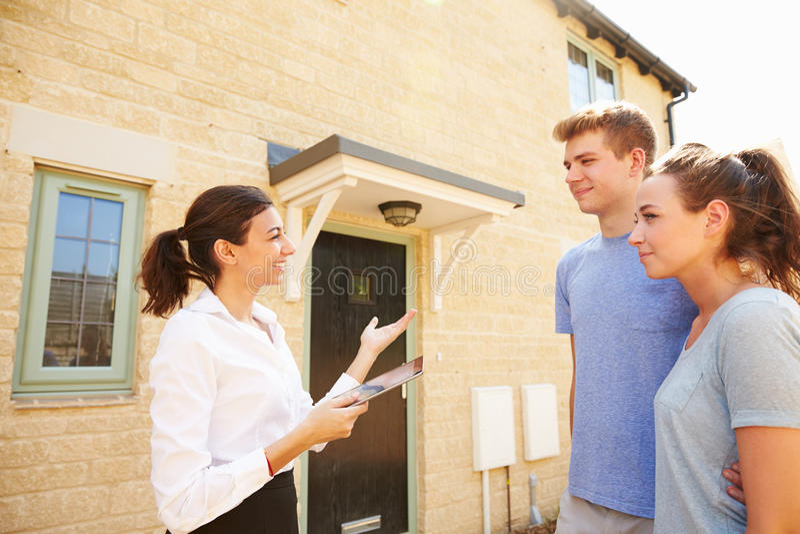 Pares jovenes que ven una casa con el agente inmobiliario de sexo femenino fotos de archivo