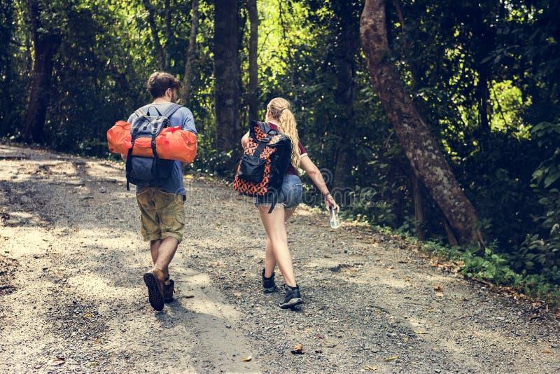 Pares jovenes que viajan así como las mochilas imagen de archivo