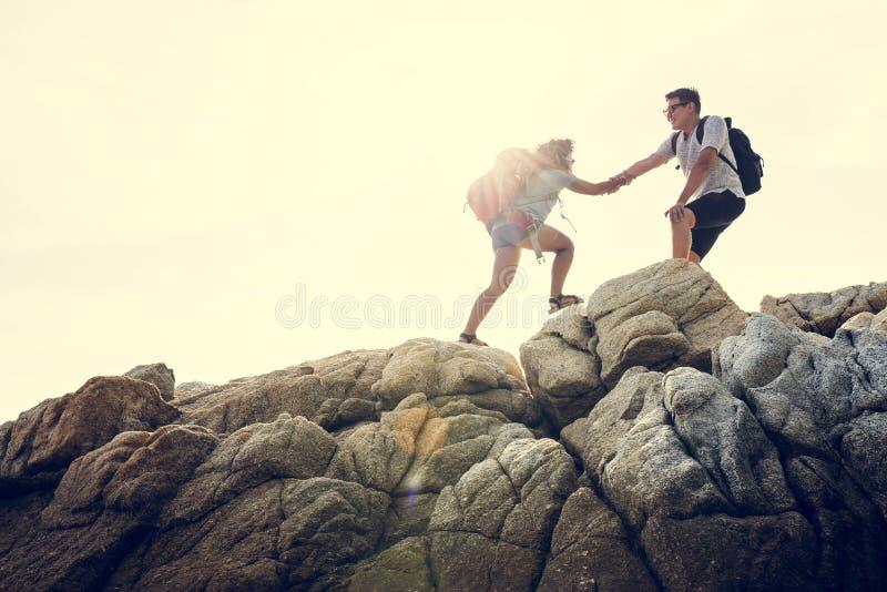 Pares jovenes que viajan junto en la colina foto de archivo