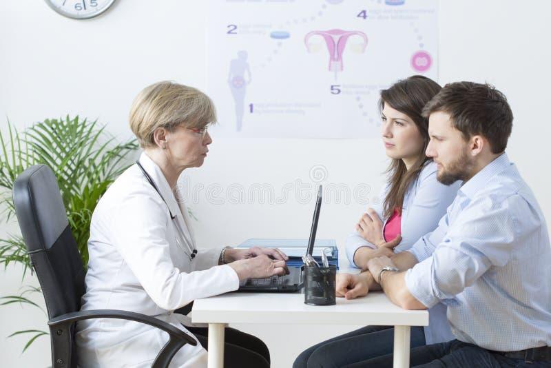 Pares jovenes que visitan a un ginecólogo foto de archivo libre de regalías