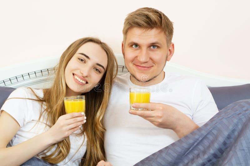 Pares jovenes relajados felices con el zumo de naranja en cama en casa Pares rom?nticos que beben el zumo de naranja que miente e fotos de archivo