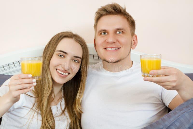 Pares jovenes relajados felices con el zumo de naranja en cama en casa Pares rom?nticos que beben el zumo de naranja que miente e fotos de archivo libres de regalías