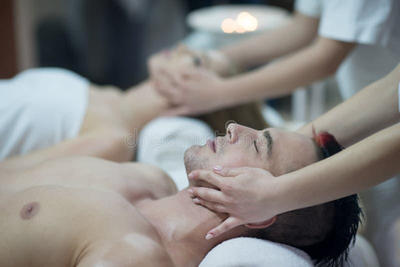 Pares jovenes relajados que consiguen masaje en balneario foto de archivo