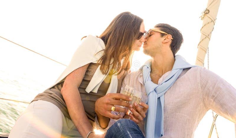 Pares jovenes ricos en amor en el velero que se besa en la puesta del sol - navegación de lujo del concepto de la forma de vida a imágenes de archivo libres de regalías