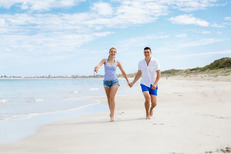 Pares jovenes románticos en la playa fotografía de archivo