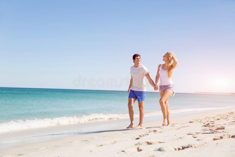 Pares jovenes románticos en la playa imagen de archivo libre de regalías
