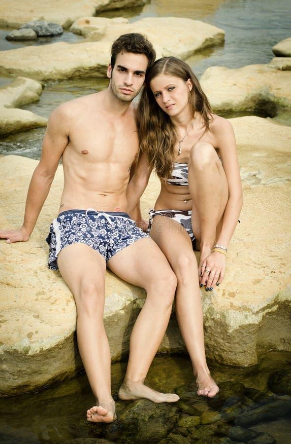 Pares jovenes románticos en traje de natación en rocas fotografía de archivo