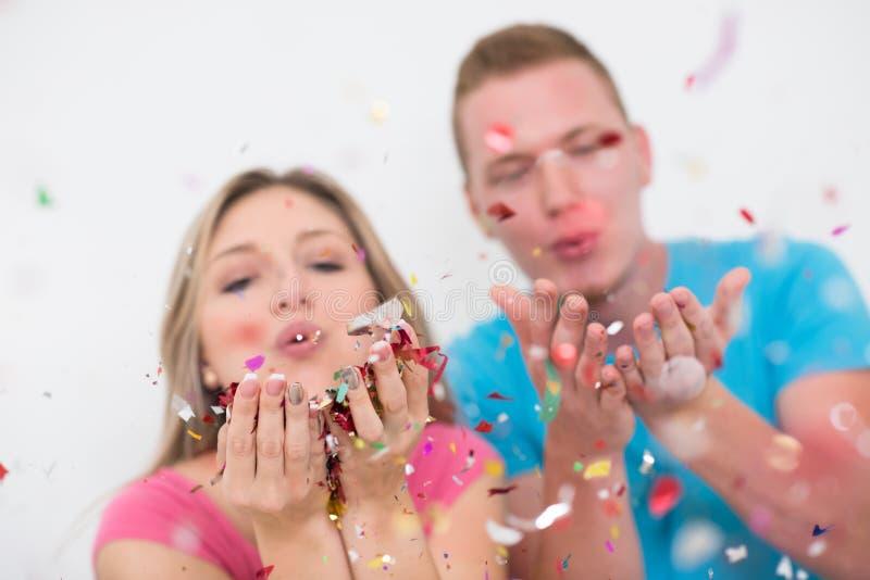 Pares jovenes románticos que celebran el partido con confeti fotografía de archivo libre de regalías